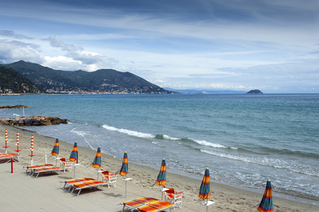 Laigueglia beach in Liguria Italy with sun loungers and umbrellas on a warm summer day Фото со стока