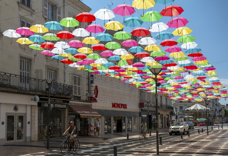Saumur, Maine-et-Loire, France - July 1, 2018: Umbrellas hanging and shading people on Rue Franklin Roosevelt in Saumur on a warm summer day