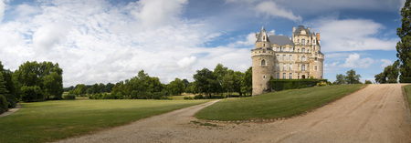 Brissac-Quince, Maine-et-Loire, France - July 2, 2018: Panoramic view of Chateau de Brissac and it's gardens on a hot summer day with clouds