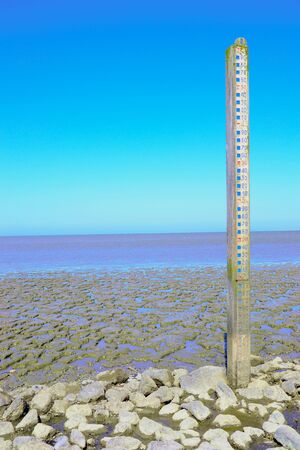 Wasserstandsanzeige im Naturgebiet in den Niederlanden. Naturlandschaft, in der das Wasser bei Hochwasser bis zu 11 Meter hoch steigen kann. Gesehen am Wattenmeer in der Nähe von Wierum, Friesland, Niederlande