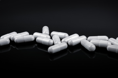 birth control pill: White pills in a row on black background Stock Photo