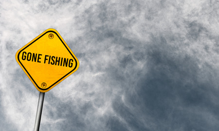 gone fishing - yellow sign with cloudy sky