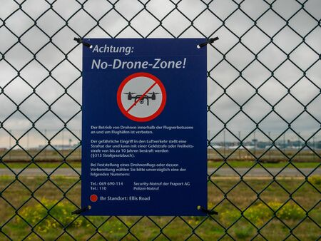 Blue Attention No-Drone-Zone Sign at Fence in Front of Fraport Frankfurt Airport, Germany