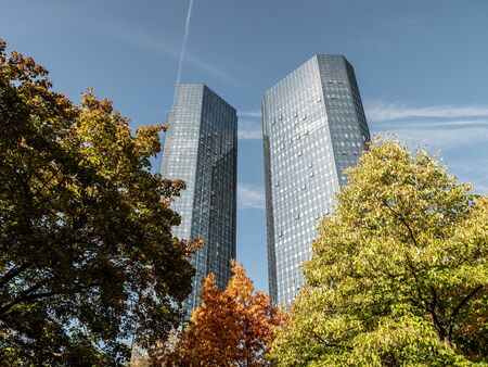 The Deutsche Bank Skyscraper low angle on a sunny day with trees in forefront, frankfurt, hessen, germany
