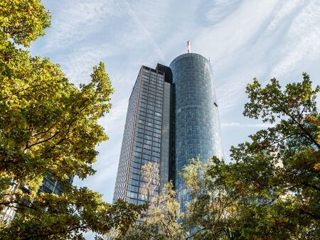 The Main Tower Skyscraper low angle with trees in forefront on a sunny day, Frankfurt, Hessen, Germany