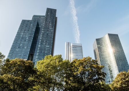 The Commerzbank, deutsche Bahn and other Skyscraper low angle with trees in forefront on a sunny day in frankfurt, hessen, germany