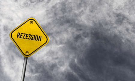 Yellow recession sign with cloudy background