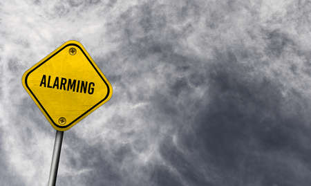 Alarming - yellow sign with cloudy background Фото со стока
