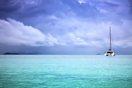A photography of a catamaran in the ocean and overcast sky photo