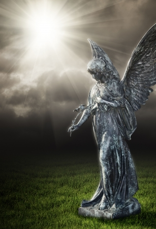 A photography of a religious angel under a dark sky Stock Photo