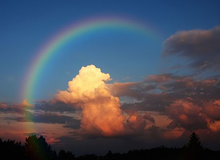 A photography of a white cloud in the evening sun under a rainbow photo