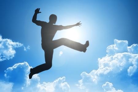 Een beeld van een springende man in de blauwe lucht