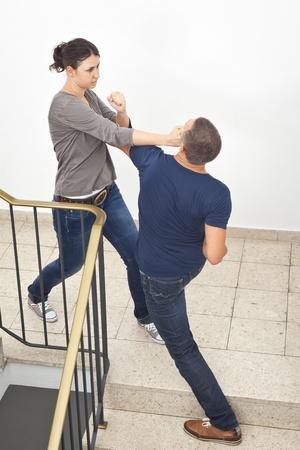 novios enojados: Una imagen de una mujer joven que lucha con un hombre Foto de archivo