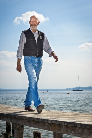 mature old generation: An old man with a grey beard is walking on a jetty Stock Photo