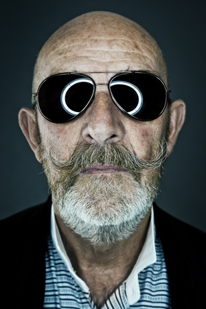 mature old generation: An old man with a grey beard wearing sunglasses
