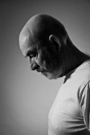Un vecchio con la barba grigia nel dolore