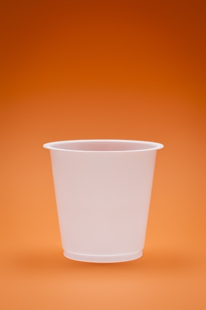 An image of a white empty plastic cup on an orange background photo