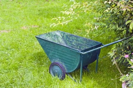 An image of an old green wheelbarrow photo
