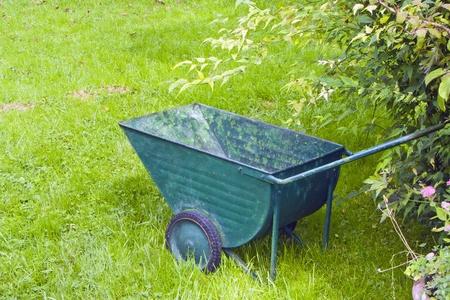 An image of an old green wheelbarrow photo