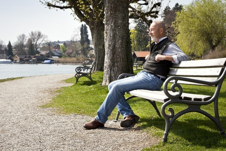 park bench: An old man is relaxing in the sun Stock Photo