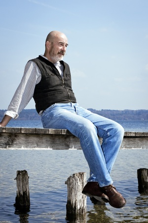 blue sky thinking: An old man with a grey beard sitting on a jetty Stock Photo