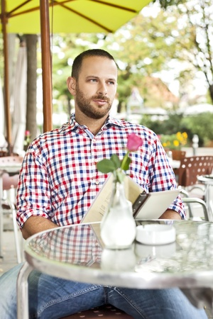 A handsome man with a beard in an outdoor coffee shop photo