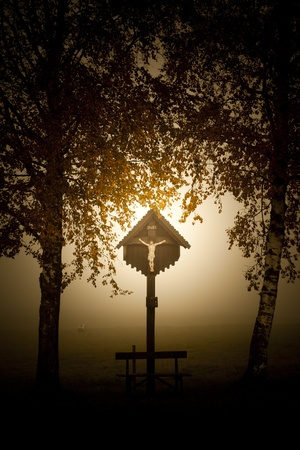 An image of a beautiful cross with fog in bavaria germany photo
