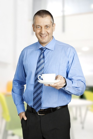 An image of a handsome business man with a cup of coffee photo
