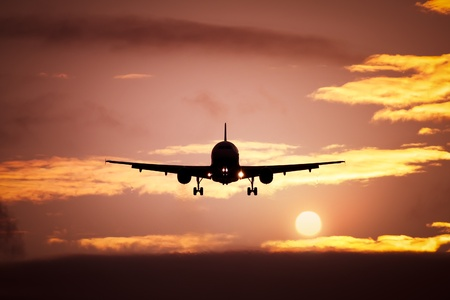 aircraft landing: An image of a plane in the sunset sky