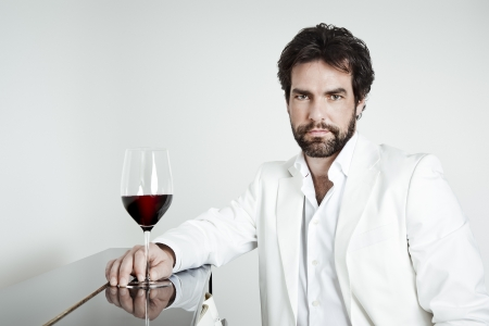 An image of a handsome man and a glass of red wine photo