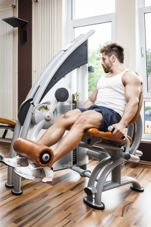 A handsome young muscular sports man doing leg press photo