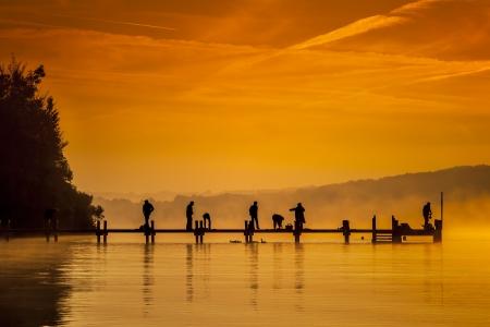wschód słońca: Stary pomost z peolpe robi wczesne sportu