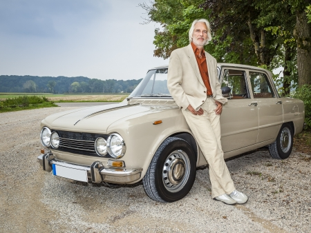 old man standing: An image of a handsome man in front of his historic car Stock Photo