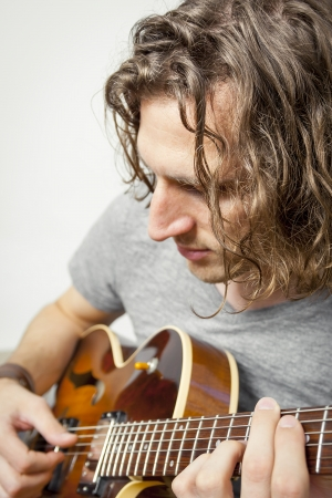 An image of a handsome man playing the guitar photo