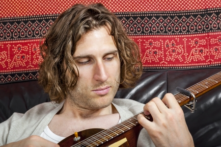 An image of a handsome guitar player with a curly hairdo photo
