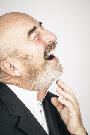 laughter: An old man with a grey beard is laughing