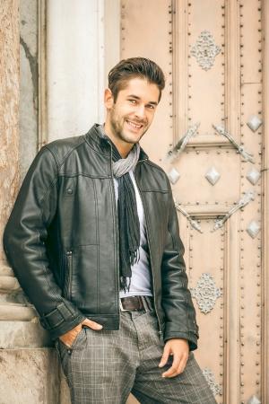 bata blanca: Una imagen de un hombre joven con una chaqueta de cuero negro Foto de archivo