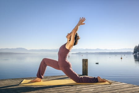 An image of a pretty woman doing yoga at the lake photo