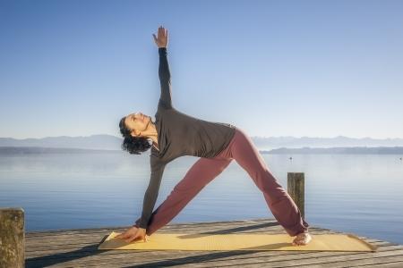 trikonasana: An image of a pretty woman doing yoga at the lake