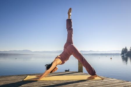 oefenen: Een afbeelding van een mooie vrouw doet yoga op het meer
