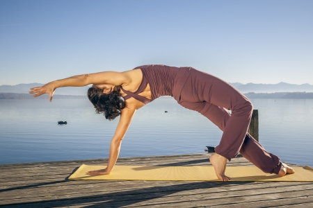 female pose: An image of a pretty woman doing yoga at the lake