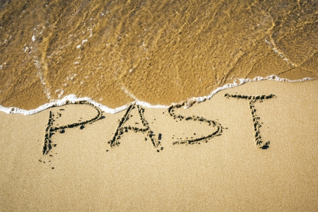 encouragement: An image of a word in the sand: PAST Stock Photo