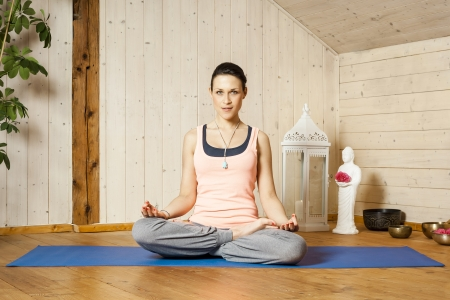 An image of a pretty woman doing yoga at home - siddhasana Stock Photo - 18032768