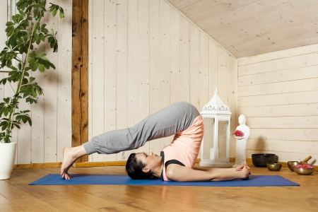 An image of a pretty woman doing yoga at home - Halasana Stock Photo - 18057704