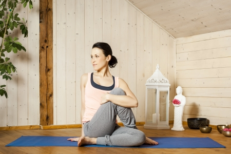 room mate: An image of a pretty woman doing yoga at home - Marichyasana