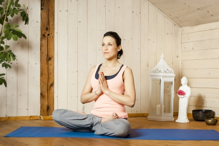 An image of a pretty woman doing yoga at home - Siddhasana Stock Photo - 18057707