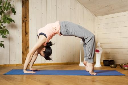 An image of a pretty woman doing yoga at home - Urdhva Dhanurasana Stock Photo - 18057700