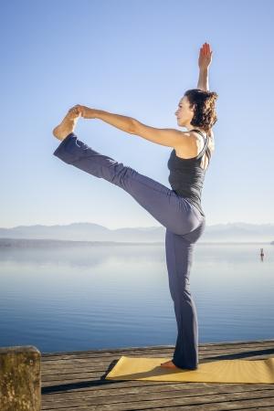 hasta: An image of a pretty woman doing yoga at the lake - Utthita Hasta Padangusthasana Stock Photo
