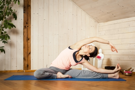 An image of a pretty woman doing yoga at home - Parivrtta Janu Shirshasana Stock Photo - 18351007