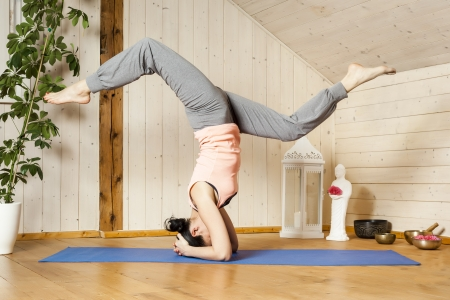 An image of a pretty woman doing yoga at home - Eka Pada Shirshasana Stock Photo - 18599426